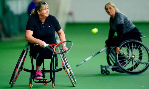 Women playing wheelchair tennis