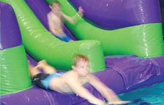 Children on inflatable water slide